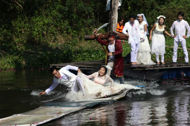Thai groom and bride, Sorawich Changtor and Rungnapa Panla, run to escape a man dressed as a pirate during a wedding ceremony ahead of Valentine's Day in Prachin Buri province