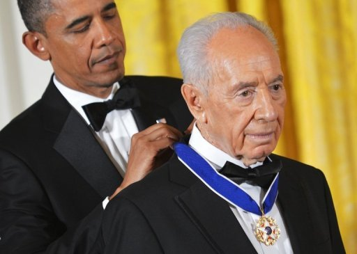 "US President Barack Obama presents Israeli President Shimon Peres with the Presidential Medal of Freedom June 13, in the White House. Obama praised Peres as the ""essence of Israel itself"" as he awarded the Israeli statesman America's highest civilian honor"