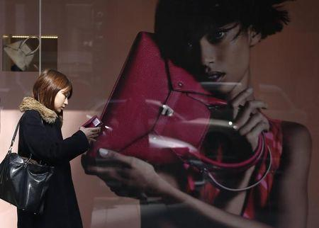 A woman walks past the display window of a luxury store at Ginza shopping district in Tokyo