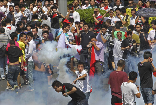 A Chinese demonstrator throws a teargas canister back to riot policemen during a protest against Japan in Shenzhen, China Sunday, Sept. 16, 2012. Protesters in China have begun another day of demonstr