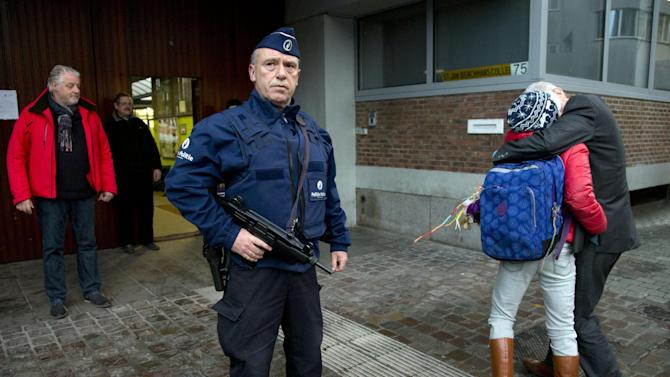 As a police officer stands guard, a man kisses his child goodbye outside the entrance of a school in the center of Brussels on Wednesday, Nov. 25, 2015. Students in Brussels have begun returning to class after a two-day shutdown over fears that a series of simultaneous attacks could be launched around the Belgian capital. (AP Photo/Virginia Mayo)