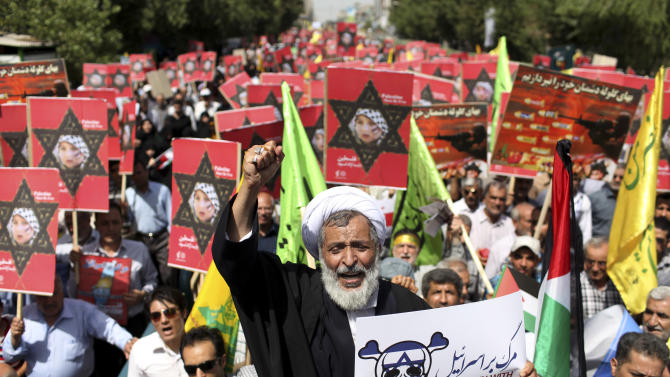 An Iranian cleric holding an anti-Israeli placard chants slogan, while attending an annual pro-Palestinian rally marking Al-Quds (Jerusalem) Day in Tehran, Iran, Friday, Aug. 2, 2013. The last Friday of the Islamic holy month of Ramadan is observed in many Muslim countries as Al-Quds day, as a way of expressing support to the Palestinians and emphasizing the importance of Jerusalem to Muslims. (AP Photo/Ebrahim Noroozi)