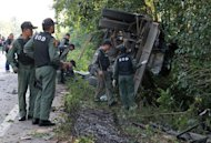 Officials inspect a damaged military patrol vehicle in Yala province following a bomb attack by suspected insurgents, on February 10, 2013. Five soldiers were killed in the attack in Thailand's violence-wracked deep south