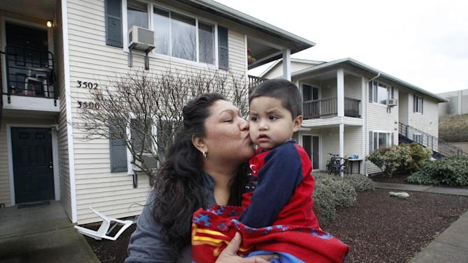 In this Feb. 28, 2012 photo, Madeline Hutchinson kisses her son Emmanuel outside their home in Salem, Ore. Pregnant with her seventh child and desperate to kick a methamphetamine habit, Hutchinson turned to a program from the local Medicaid provider that connected her with a mentor and other support that helped her stay off drugs and give birth to a healthy boy. Emmanuel, now 2, was born drug-free and is the only one of her children still in her custody. But Hutchinson's health provider can't get reimbursed for much of the treatment she credits with saving her life, keeping her healthy and protecting the health of her child.(AP Photo/Rick Bowmer)
