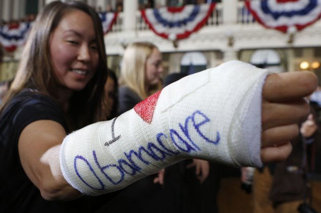 "Cathey Park of Cambridge, Massachusetts holds out her cast with ""I Love Obamacare"" written upon it prior to U.S. President Barack Obama's arrival to speak about health insurance at Faneuil Hall in Boston October 30, 2013. REUTERS/Kevin Lamarque (UNITED STATES - Tags: POLITICS)"