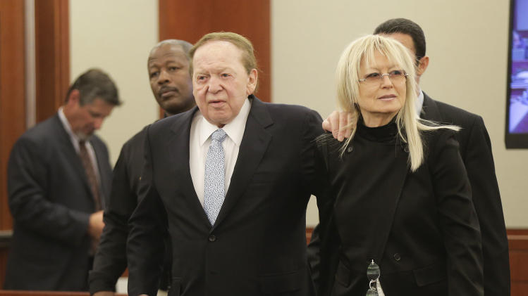 Las Vegas Sands Corp. CEO Sheldon Adelson, left, walks into the courtroom with his wife Miriam before taking the witness stand, Thursday, April 4, 2013, in Las Vegas. The casino billionaire and GOP super-donor  made a rare public appearance, Thursday, as the lead witness against a Hong Kong businessman who is suing his company for $328 million. (AP Photo/Julie Jacobson)