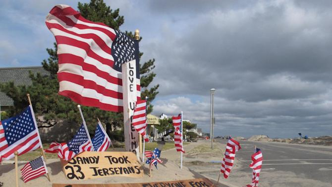 Superstorm Sandy washed so much sand from the beach across Ocean Avenue to the other side of the roadway in Belmar N.J. that someone erected a monument in a sand pile in Belmar, N.J. thanking rescue workers, as seen in this Nov. 15, 2012 photo. Superstorm Sandy took a bite out of the Jersey shore, washing away millions of tons of sand and slimming down beaches along the state's 127-mile coastline. (AP Photo/Wayne Parry)