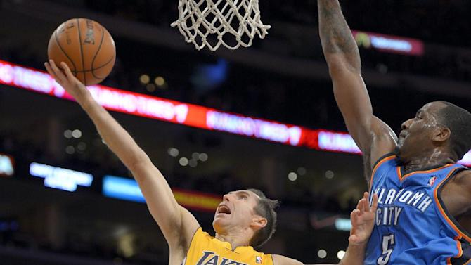 Los Angeles Lakers guard Steve Nash, left, shoots around Oklahoma City Thunder center Kendrick Perkins during the first half of their NBA basketball game, Friday, Jan. 11, 2013, in Los Angeles. (AP Photo/Mark J. Terrill)