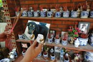 "A visitor holding a photograph of his dead pet dog prepares to place incense sticks on an altar for dead pets at a private hotel for pets in Hanoi. The establishment offers ""hotel rooms"" for pets whose owners go away on business or holidays -- and even has a cemetery for dogs and cats"