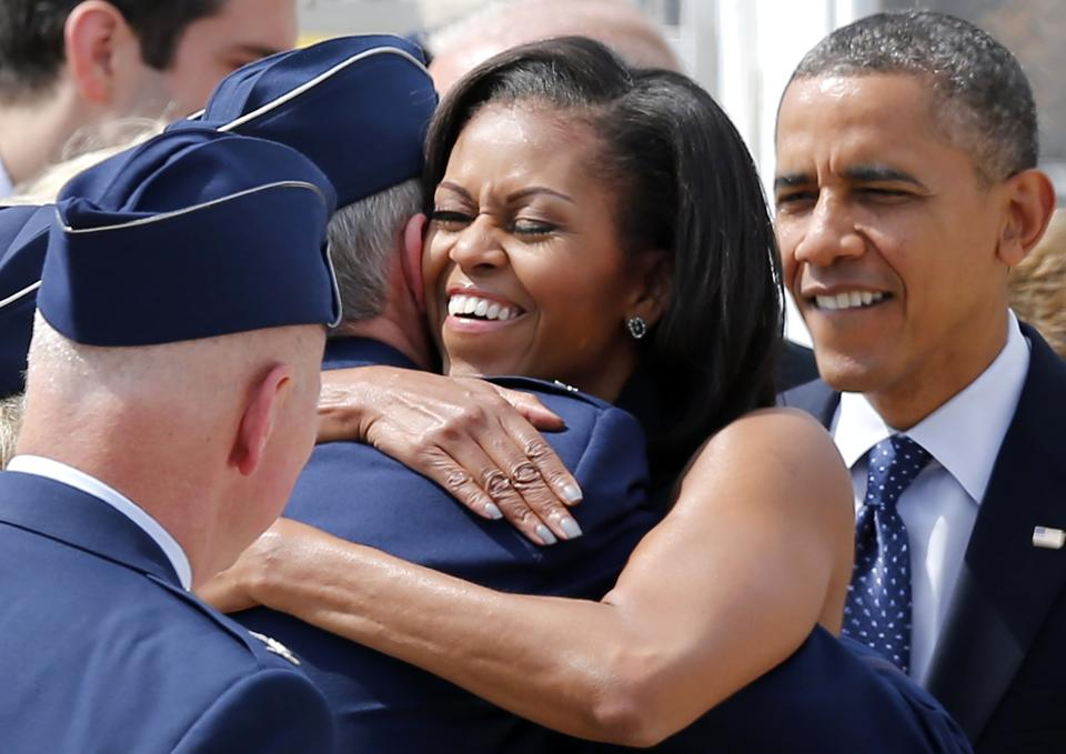 President Barack Obama watches as his wife, first lady Michelle Obama, greets service members upon their arrival at Pease Air National Guard Base in Portsmouth, N.H., Friday, Sept. 7, 2012. (AP Photo/Winslow Townson)