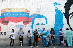 People stand by a mural of Hugo Chavez in Petare