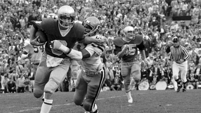 FILE - In this Nov. 7, 1977, file photo, Notre Dame's Joe Montana tries to brush off Georgia Techs' Reggie Wilkes on a 6-yard gain in the first quarter of an NCAA college football game at South Bend, Ind. (AP Photo/FHJ, File)