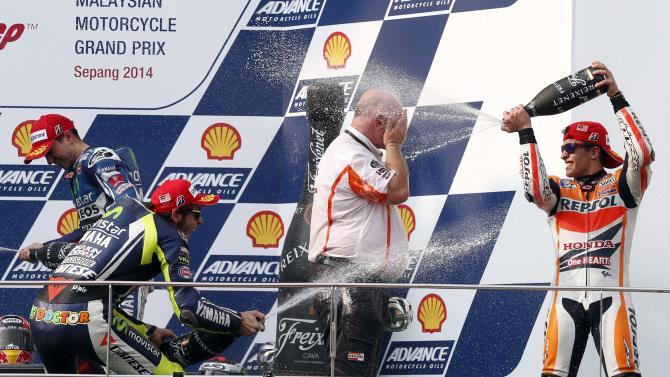 Yamaha MotoGP rider Valentino Rossi and Honda MotoGP rider Marc Marquez spray champagne on team official Roger Van Der Borght at Sepang International Circuit