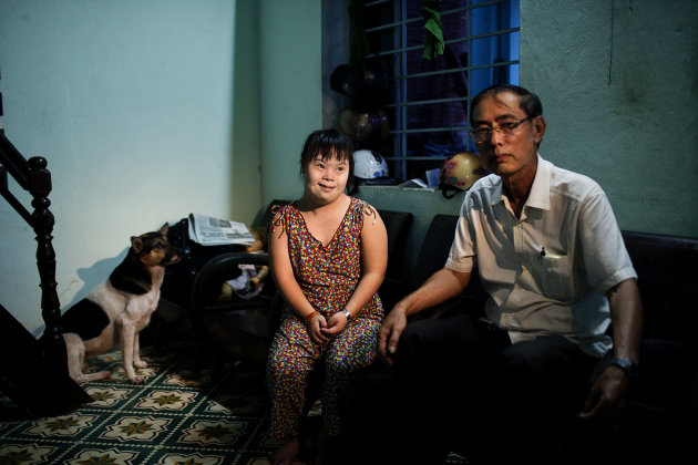 In this photo taken Aug. 7, 2012, Vo Thi Thuy Nga, 24, left, and her uncle Vo Duoc sit inside their home in Danang, Vietnam. She was born with physical and mental disabilities that a rehabilitation ce