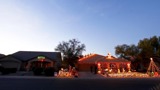 """Unable to compete with her neighbor, Eric Cyr, Kristina Green opted to decorate her home, left, with a 450-light """"Ditto"""" sign and an arrow pointing to Cyr's 20,000-light Christmas display, as shown Tuesday, Dec. 11, 2012 in Maricopa, Ariz. (AP Photo/Ross D. Franklin)"""