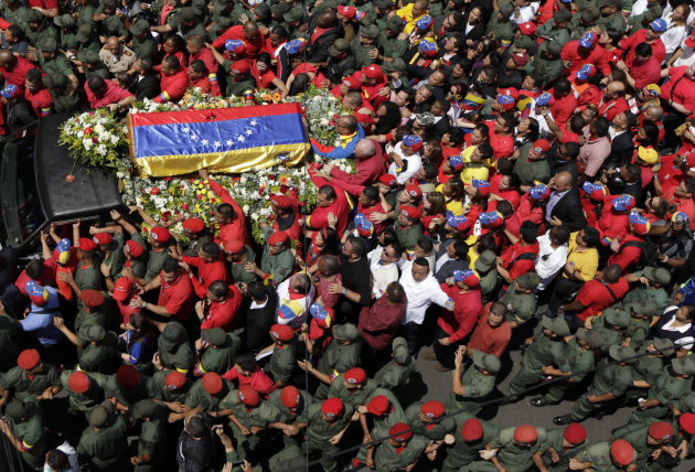 People walk alongside the flag-draped coffin containing the body of Venezuela's late President Hugo Chavez from the hospital where he died, to a military academy where it will remain until his funeral