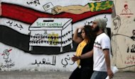 Egyptians walk past graffiti depicting a chained ballot box being controlled by the ruling military council at Tahrir Square in Cairo
