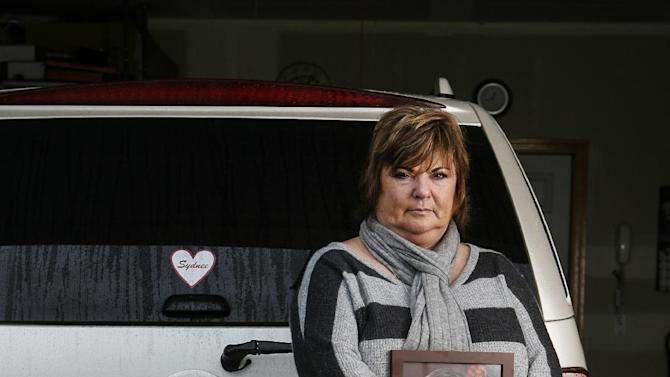In this Saturday, Dec. 22, 2012 photo, Judy Neiman holds a photo of her daugher, Sydnee, in front of her 2006 Cadillac Escalade at her home in West Richland, Wash. Sydnee died in late 2011 after Neiman accidentally backed over her with the SUV. Although there is a law in place that calls for new manufacturing requirements to improve the visibility behind passenger vehicles, the standards have yet to be mandated because of delays by the U.S. Department of Transportation. (AP Photo/Kai-Huei Yau)