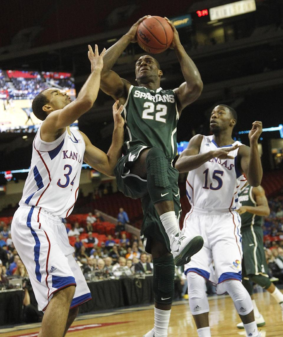 Michigan State guard Branden Dawson (22) drives the lane between Kansas forward Perry Ellis (34) and guard Elijah Johnson (15)during the first half of an NCAA college basketball game at the Georgia Dome in Atlanta Tuesday, Nov. 13, 2012. (AP Photo/John Bazemore)