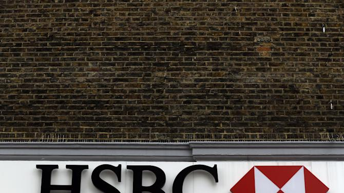 The nameplate sign above a branch of the HSBC bank in London, Wednesday, May 15, 2013, after the bank announced 2 to 3 billion US dollars in new cuts as it continues to trim its global empire. Europe's biggest bank by market value, HSBC announced a doubling of its profit earlier this month as it reaped the benefits of recent restructuring, trimming around 40,000 jobs from a workforce of about 300,000 since 2011, but the new cost cutting is widely expected to translate into additional layoffs. (AP Photo/Lefteris Pitarakis)
