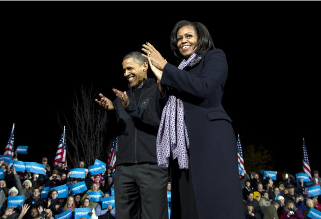 President Barack Obama and first lady Michelle Obama acknowledge the crowd at his final campaign stop on the evening before the 2012 election, Monday, Nov. 5, 2012, in the downtown Des Moines, Iowa. (