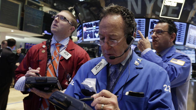 Trader Steven Kaplan, center, works on the floor of the New York Stock Exchange Friday, May 16, 2014. The stock market is little changed in early trading following sharp declines the previous day. (AP Photo/Richard Drew)