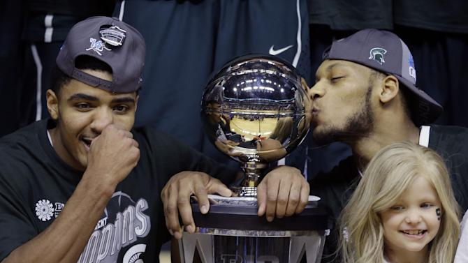 "FILE - In this March 16, 2014 file photo, Michigan State's Gary Harris, left, poses with the championship trophy as Adreian Payne kisses it after they defeated Michigan 69-55 in an NCAA college basketball game in the championship of the Big Ten Conference tournament in Indianapolis. Lacey Holsworth, who is batling cancer, smiles at right foreground. The father of 8-year-old Lacey Holsworth, who befriended Michigan State basketball star Adreian Payne says his daughter has died. Matt Holsworth says Lacey Holsworth died at their St. Johns, Mich., home late Tuesday, April 8, 2014, ""with her mommy and daddy holding her in their arms.""(AP Photo/Michael Conroy)"