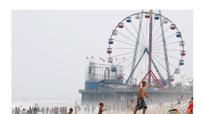 In this combination of two file photos, the Funtime Pier in Seaside Heights, N.J. is shown before and after superstorm Sandy made landfall on the Jersey Shore. At top in this Aug. 10, 2010 file photo, the Funtime Pier rises from the sand and surf at Seaside Heights on the New Jersey coast. Below, Funtime Pier Owner Billy Major surveys the damage on Wednesday, Oct. 31, 2012 after superstorm Sandy tore through the region and left only four rides standing. Top (AP Photo/Mel Evans) Bottom (AP Photo/Star-Ledger, David Gard/POOL)