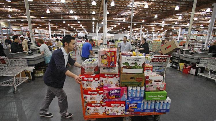 FILE- In this Wednesday, May 9, 2012, file photo, David Lee shops at a Costco Wholesale store, in Portland, Ore. U.S. wholesale companies added modestly to their stockpiles in May. But sales at the wholesale level dropped by the largest amount in three years, a troubling sign for future growth. (AP Photo/Rick Bowmer, File)