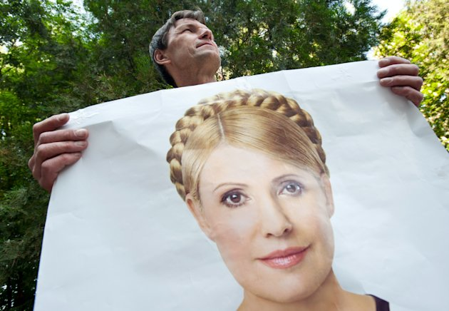 A supporter of former Ukrainian Prime Minister Yulia Tymoshenko holds a poster of her in front of a state-run hospital in Kharkiv, Ukraine, Wednesday May 9, 2012. Tymoshenko, Ukraine's imprisoned former prime minister, was moved Wednesday from jail to this hospital for treatment of a severe back condition under the supervision of a German doctor. The move was likely to allay at least some Western concerns over Tymoshenko's health and handling in prison. Top EU officials and some EU governments have vowed to boycott the European football championship matches co-hosted by Ukraine in June, and Ukraine had to cancel a regional cooperation summit this weekend after most heads of central and eastern European states canceled their visits over the Tymoshenko case. (AP Photo/dapd/ Alexey Furman)