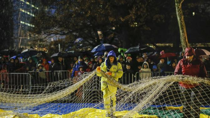Members of the Macy's Thanksgiving Day Parade balloon inflation team secure a balloon during preparations for the 88th annual Macy's Thanksgiving Day Parade in New York