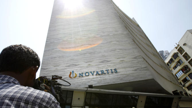 A cameraman films the head office of Novartis India Limited in Mumbai, India, Monday, April 1, 2013. India's Supreme Court on Monday rejected drug maker Novartis AG's attempt to patent a new version of a cancer drug Glivec, in a landmark decision that healthcare activists say ensures poor patients around the world will get continued access to cheap versions of lifesaving medicines. (AP Photo/Rafiq Maqbool)