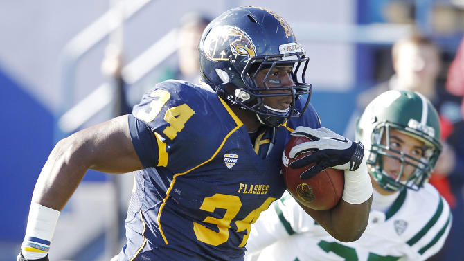 Kent State's Trayion Durham rushes past Ohio's Devin Bass for a touchdown during the first quarter of an NCAA college football game, Friday, Nov. 23, 2012, in Kent, Ohio.  (AP Photo/Ron Schwane)