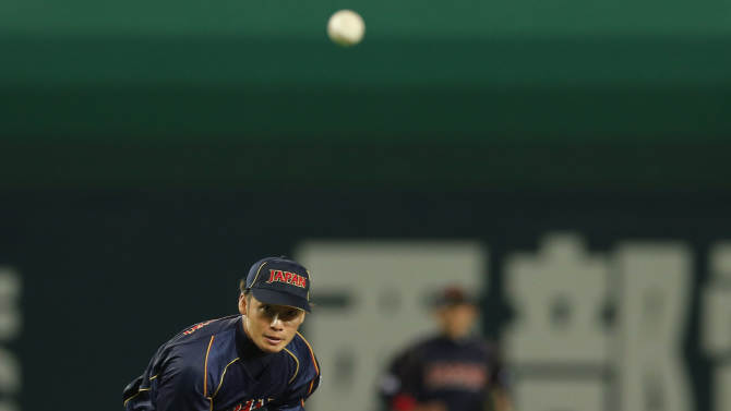 Japan's second baseman Takashi Toritani throws to first to complete a double play as Brazil's right fielder JC Muniz slide into second in the second inning of their World Baseball Classic first round game in Fukuoka, Japan, Saturday, March 2, 2013. (AP Photo/Koji Sasahara)