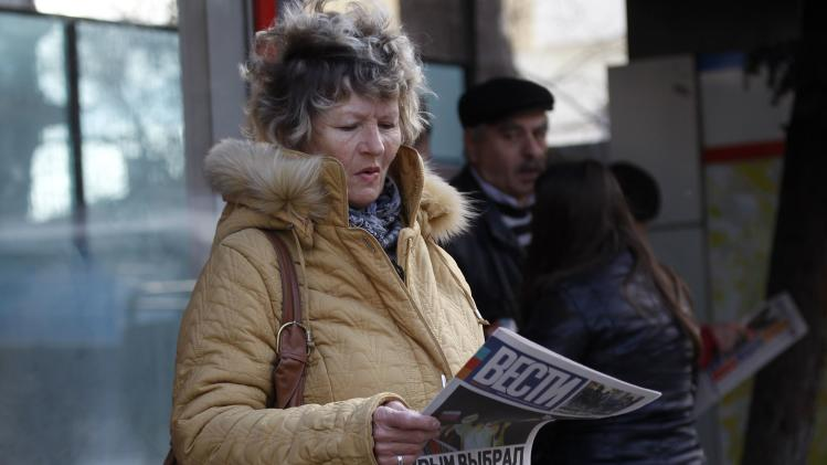 "A woman reads a free newspaper with headline ""Crimea chooses Russia"" on a street in Simferopol"