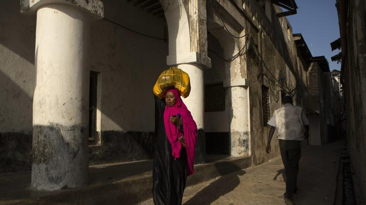 A woman carrying her belongings walks along a street of Lamu town, the main settlement in Lamu, an island in the Indian Ocean off the northern coast of Kenya