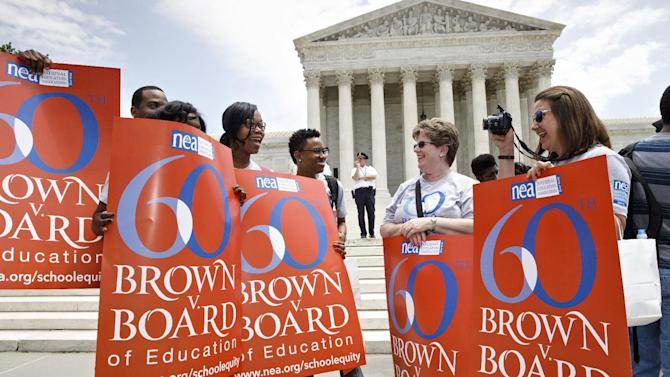 "This photo taken May 13, 2014 shows National Education Association staff members from Washington joining students, parents and educators at a rally at the Supreme Court in Washington on the 60th anniversary Brown v. Board of Education decision that struck down ""separate but equal"" laws that kept schools segregated. Saturday marks the 60th anniversary of the landmark Brown v. Board of Education decision. Many inequities in education still exist for black students and for Hispanics, a population that has grown exponentially since the 1954 ruling. (AP Photo)"