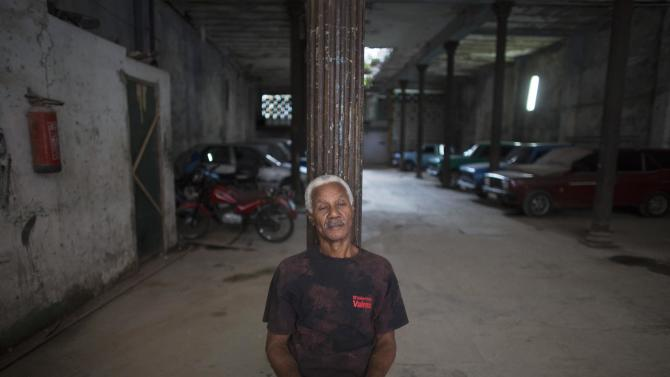 Caretaker Juanito Vallestin sits in a public parking in downtown Havana