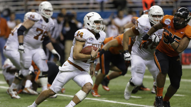 Texas' David Ash (14) rushes as Oregon State's Scott Crichton, right, moves in during the fourth quarter of the Alamo Bowl NCAA football game, Saturday, Dec. 29, 2012, in San Antonio.  Texas won 31-27. (AP Photo/Eric Gay)