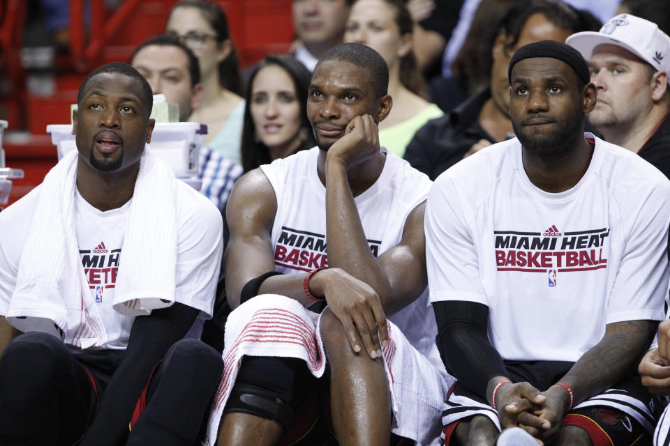 Miami Heat guard Dwyane Wade, left, forward Chris Bosh, and forward LeBron James, right, sit on the bench during the fourth quarter of a preseason NBA basketball game against the New Orleans Hornets, Friday, Oct. 26, 2012 in Miami. The Hornets defeated the Heat 96-89. (AP Photo/Wilfredo Lee)