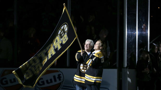 """William and Patricia Campbell, parents of Krystle Campbell, who was killed in the Boston Marathon bombings, wave a """"Boston Strong"""" banner before Game 4 in the Eastern Conference finals of the NHL hockey Stanley Cup playoffs between the Boston Bruins and the Pittsburgh Penguins, in Boston on Friday, June 7, 2013. (AP Photo/Elise Amendola)"""
