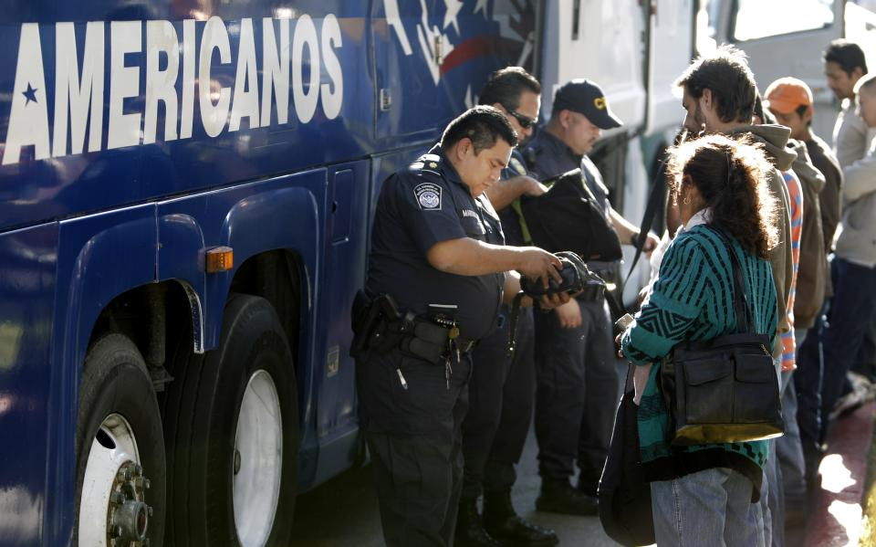 In this Dec. 9, 2010 photo, U.S. Customs and Border Protection agents check the documents of southbound passengers heading from the U.S. to Mexico, in Brownsville, Texas.  Customs agents are trying to stem the smuggling of guns and cash from the U.S. to Mexico. (AP Photo/LM Otero)