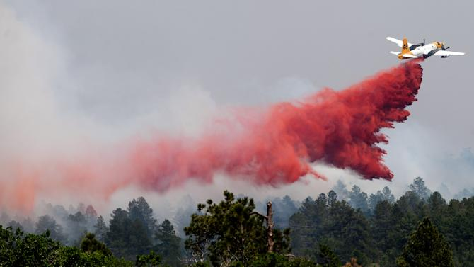 A slurry bomber makes a pass over the Black Forest fire north of Colorado Springs, Colo., Thursday, June 13, 2013. A voracious wildfire driven in all directions by shifting winds destroyed at least 360 homes — a number that was likely to climb as the most destructive blaze in Colorado history burned out of control for a third day through miles of tinder-dry woods. (AP Photo/The Colorado Springs Gazette, Michael Ciaglo)  MAGS OUT