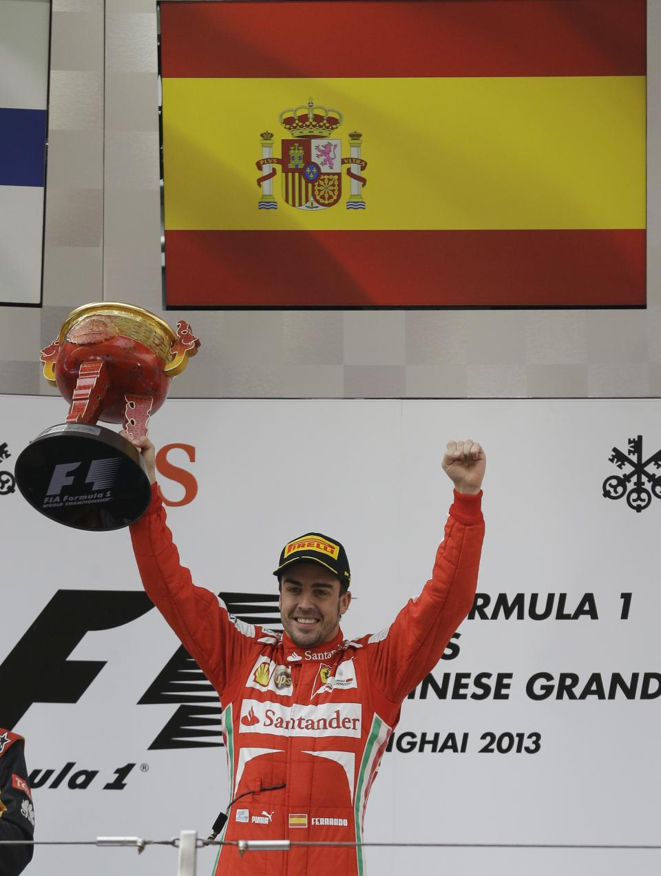 Ferrari driver Fernando Alonso of Spain holds his trophy aloft as he celebrates his win at the Chinese Formula One Grand Prix in Shanghai, China, Sunday, April 14, 2013. (AP Photo/Ng Han Guan)