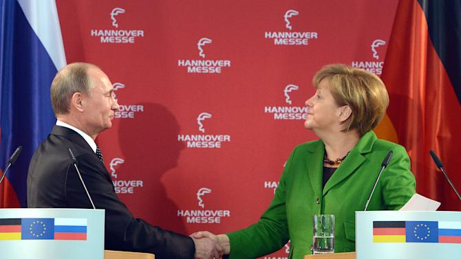 German chancellor Angela Merkel, right, and Russian Presideent Vladimir Putin shake hands after a press conference at the Hannover Fair, in Hannover, northern Germany, Monday April 8, 2013. (AP Photo/dpa, Marcus Brandt)