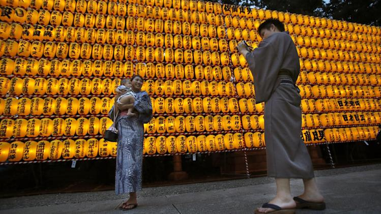 "Visitors take a photo in front of rows of paper lanterns during the festival of ""Mitama"", or departed souls at Yasukuni shrine in Tokyo, Monday, July 14, 2014. The devotees' names of the shrine are seen on the lanterns. (AP Photo/Shizuo Kambayashi)"
