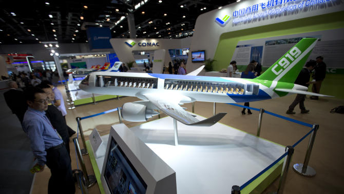 Visitors check a model of China's homegrown commercial jet C919, intended to compete with Boeing's 737 and the Airbus A320, at an aviation expo in Beijing, Wednesday, Sept. 25, 2013. Delays in the 90-seat ARJ21 could have knock-on effects for the development of the bigger and more ambitious C919, intended to compete with Boeing's 737 and the Airbus A320. (AP Photo/Alexander F. Yuan)
