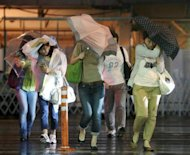 People try to hold on to their umbrellas under heavy winds and rain brought on by Typhoon Jelawat, in front of a railway station in Tokyo, on September 30. The typhoon left at least two people dead and more than 180 injured over the weekend before passing out into the Pacific on Monday