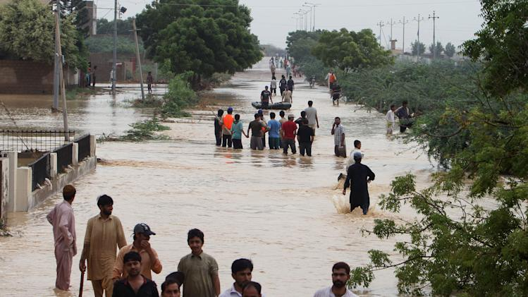 People wade through flooded road caused by heavy rains on the outskirts of Karachi, Pakistan, Sunday, Aug. 4, 2013. Heavy rains that swept across Pakistan brought down more than 100 homes and caved in a factory wall, killing at least a dozen people in the downpours, officials said. (AP Photo/Fareed Khan)