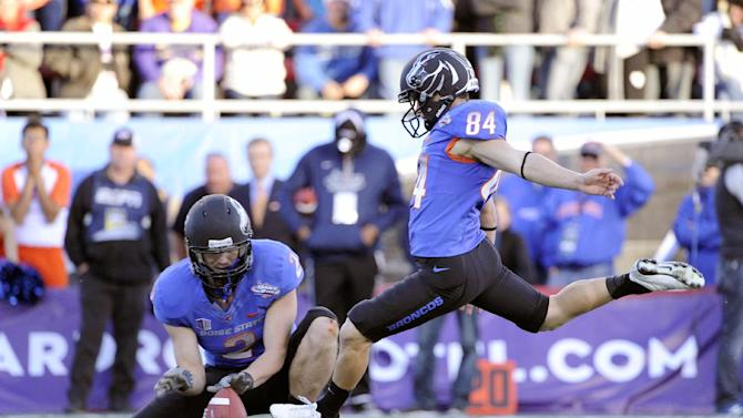 Boise State Matt Miller (2) holds the ball for kicker Michael Frisina (84) who boots the ball during the final minutes of the MAACO Bowl NCAA college football game on Saturday, Dec. 22, 2012, in Las Vegas. The field goal was the go-ahead for Boise State to defeat Washington 28-26. (AP Photo/David Becker)